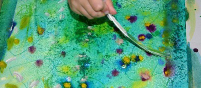 Eine Hand, die mit einer Feder malt