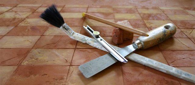 Auf Fliesenboden liegt Handwerkszeug zum Malen (Pinsel, Spachtel, Stift, Stein und Cutter)